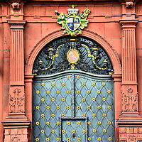 Mainz Coat of Arms in Mainz, Germany <br /> In the center of this elaborate door on the Rhine River side of the Deutschhaus are two wheels that each have six spokes and are connected with a cross.  This is the coat of arms for the town of Mainz, Germany.  It dates back to 780 when this symbol was used by the Archbishop-Elector of Mainz as the powerful leader of the Imperial Diet of the Holy Roman Empire.