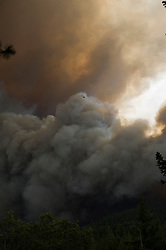 September 12, 2015 - Lake County, California. Smoke and flames erupted in Boggs Mountain State Forest remains in close observation of Cal Fire spotter aircraft,  viewed from Loch Lomond. (Kim Ringeisen / Polaris)