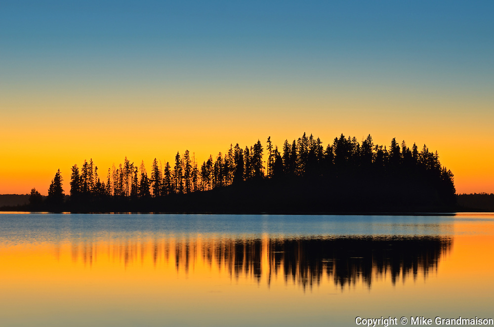 Island reflected in Astotin Lake at sunrise<br /> Elk Island National Park<br /> Alberta<br /> Canada<br /> Elk Island National Park<br /> Alberta<br /> Canada