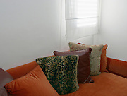 Cushions of various colours on a sofa and white Curtains on a window
