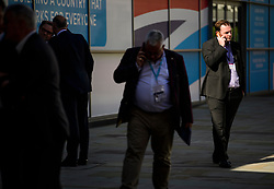 © Licensed to London News Pictures. 03/10/2017. Manchester, UK. A delegate on his mobile phone, outside the conference venue, on day three of the Conservative Party Conference. The four day event is expected to focus heavily on Brexit, with the British prime minister hoping to dampen rumours of a leadership challenge. Photo credit: Ben Cawthra/LNP