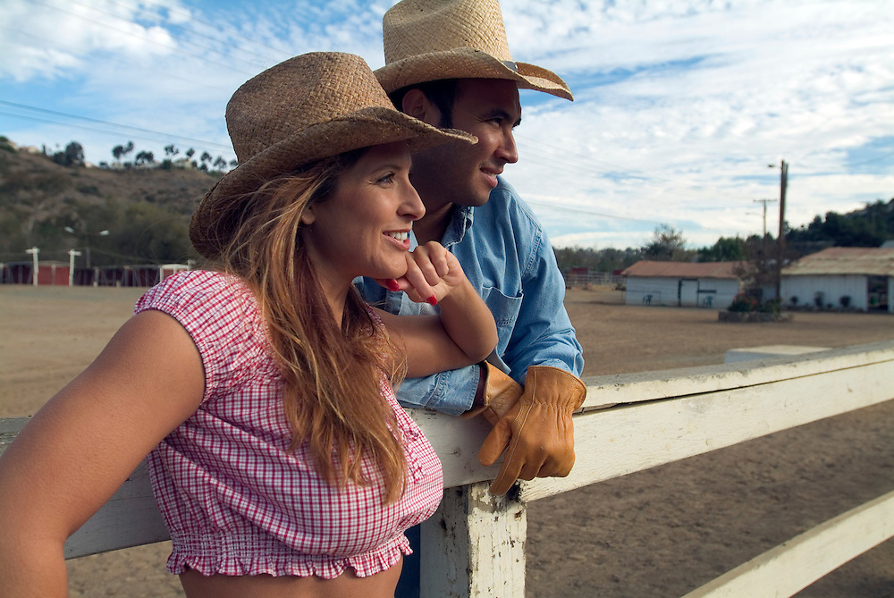 Lifestyle portrait of rancher and his wife watching horses in a corral in San Diego, CA.