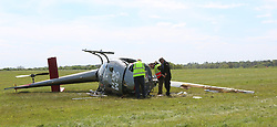 High Wycombe Buckinghamshire Friday 5th May 2017 <br /> High Wycombe helicopter crash: Man fighting for life<br /> <br /> Three people travelling in the aircraft were on the ground outside when ambulance crews arrived at the scene.<br /> <br /> A man is in hospital with life-threatening injuries after a helicopter crash.<br /> <br /> Three men were in the aircraft when it came down at Wycombe Air Park near High Wycombe, in Buckinghamshire.<br /> <br /> <br /> <br /> The helicopter was resting on its side and the occupants outside on the grass when ambulance crews arrived at the scene.<br /> <br /> The two most serious casualties were taken to the major trauma unit at John Radcliffe Hospital in Oxford.<br /> <br /> One suffered life-threatening injuries, while another had serious head, chest, leg, abdominal and shoulder injuries.<br /> <br /> <br /> I<br /> The third man suffered &quot;less serious back injuries&quot;, South Central Ambulance Service said. He was taken to hospital in Slough.<br /> <br /> Emergency services were alerted shortly after 9.30am.<br /> <br /> One of the first at the scene was an off-duty paramedic, who was at the airport waiting for his own flying lesson.<br /> <br /> He provided treatment to the most seriously injured patient before ambulance crews arrived.<br /> <br /> The Air Accidents are now at the scene carrying out there investigation&copy;UKNIP
