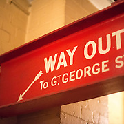 An emergency exit sign at the Churchill War Rooms in London. The museum, one of five branches of the Imerial War Museums, preserves the World War II underground command bunker used by British Prime Minister Winston Churchill. Its cramped quarters were constructed from a converting a storage basement in the Treasury Building in Whitehall, London. Being underground, and under an unusually sturdy building, the Cabinet War Rooms were afforded some protection from the bombs falling above during the Blitz.