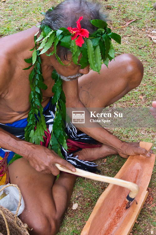Yapese man in traditional clothing making craft, wood carving, at Yap Day Festival, Yap Island, Federated States of Micronesia