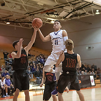 Noah Nells (11) of Miyamura goes hard to the basket as Cord Cox (40) and Luke Nelson (12) of Artesia try to defend during the Gallup Invitational Tournament game in Gallup. Miyamura won 63-56.