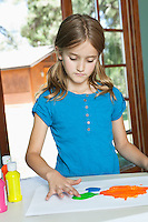 Little girl finger painting on paper at table