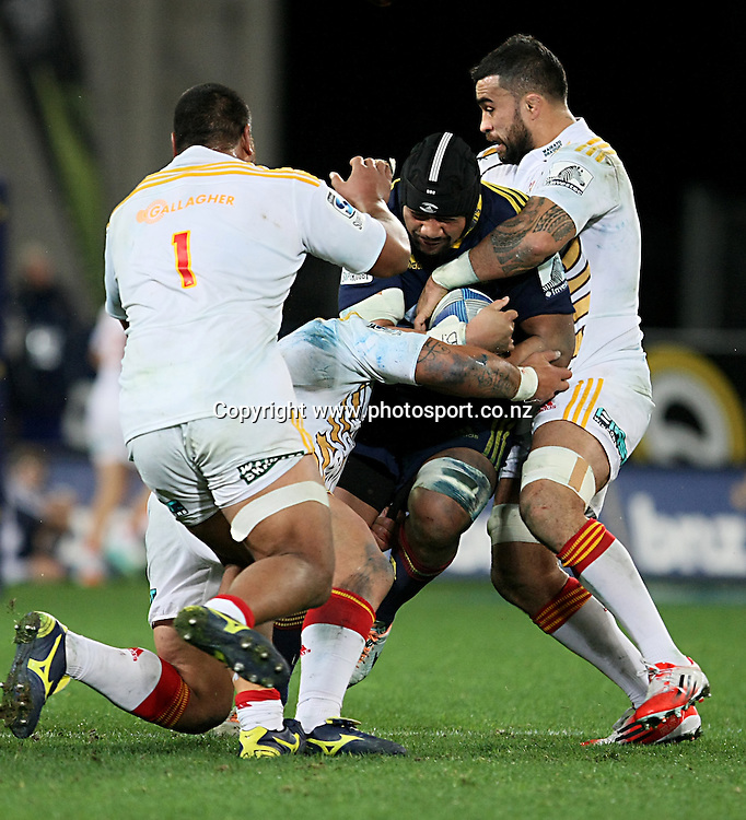 Nasi Manu of the Highlanders, centre, in the tackle of Liam Messam of the Chiefs, right, in the Super 15 rugby match, Highlanders v Chiefs, Forsyth Barr Stadium, Dunedin, New Zealand, Friday, June 27, 2014. Photo: Dianne Manson / www.photosport.co.nz