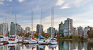 Condo and apartment towers behind the yachts at the Vancouver Rowing Club and fall foliage in Devonian Harbour Park. Photographed from the Stanley Park seawall along the western end of Coal Harbour in Vancouver, British Columbia, Canada