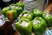 Peppers filled with rice have been just cooked at a Freegan dinner made entirely with food recovered from dumping sites around the island of Manhattan, New York, NY., on Friday, June 23, 2006. Freegans are a community of people who aims at recovering wasted food, books, clothing, office supplies and other items from the refuse of retail stores, frequently discarded in brand new condition. They recover goods not for profit, but to serve their own immediate needs and to share freely with others. According to a study by a USDA-commissioned study by Dr. Timothy Jones at the University of Arizona, half of all food in the United States is wasted at a cost of $100 billion dollars every year. Yet 4.4 million people in the United States alone are classified by the USDA as hungry. Global estimates place the annual rate of starvation deaths at well over 8 million. The massive waste generated in the process fills landfills and consumes land as new landfills are built. This waste stream also pollutes the environment, damages public health as landfills chemicals leak into the ground, and incinerators spew heavy metals back into the atmosphere. Freegans practice strategies for everyday living based on sharing resources, minimizing the detrimental impact of our consumption, and reducing and recovering waste and independence from the profit-driven economy. They are dismayed by the social and ecological costs of an economic model where only profit is valued, at the expense of the environment. In a society that worships competition and self-interest, Freegans advocate living ethical, free, and happy lives centred around community and the notion that a healthy society must function on interdependence. Freegans also believe that people have a right and responsibility to take back control of their time.