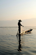 Burma/Myanmar, Inle Lake. Fishermen from Inle Lake.<br /> <br /> They're especially famous for their unique way of rowing. Unlike others, Intha fishermen use their legs to row their small boats, so that they have free hands. By balancing on the helm and paddling in a circular motion with one leg they make their boats moving.<br /> They also use special tall conical nets to catch fish. Rowing with legs allows them to drop nets over passing fish, which they can spot in the clear and shallow water.