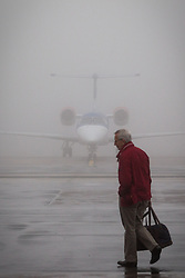© Licensed to London News Pictures . 09/01/2013 . Manchester , UK . A passenger crosses the tarmac to board a plane as behind him an aeroplane sits on the ground in thick fog . Thick fog is causing flight delays and cancellations in the North of England today (9th January 2013) . Photo credit : Joel Goodman/LNP