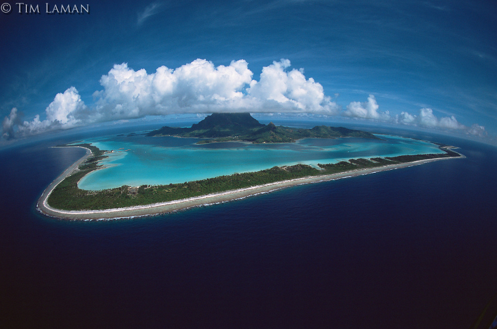 Puffy clouds fill the sky over Bora Bora Island, Society Islands, French Polynesia.  June 2002.