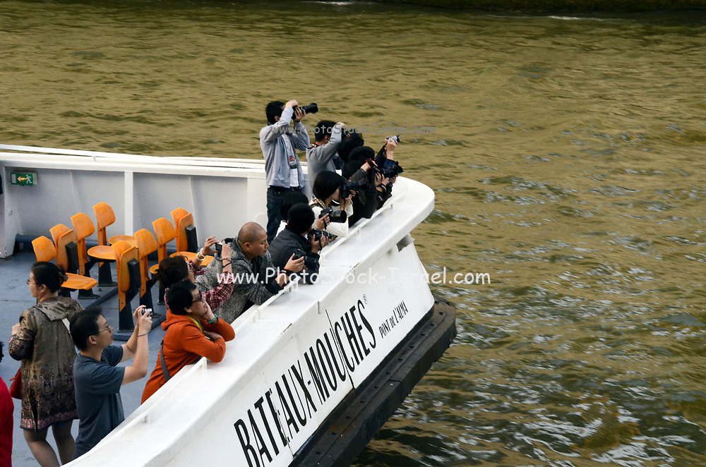 Tourists on a boat on the river Seine in the heart of Paris, France