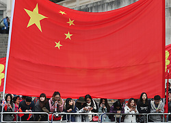 © Licensed to London News Pictures. 20/10/2015. London, UK. Supportrs of Chinese President Xi Jinping use their phones as they wait in The Mall in front of a giant Chinese flag as a four day State Visit to the United Kingdom gets under way. Photo credit: Peter Macdiarmid/LNP