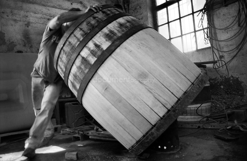 Turning the barrel to assure an even heat of the wood.
