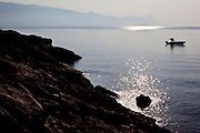 A man starts a motor boat in the Adriatic Sea off the coast of Brac Island, Croatia.