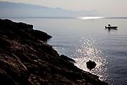 A man starts a motor boat in the Adriatic Sea off the coast of Brac Island, Croatia.