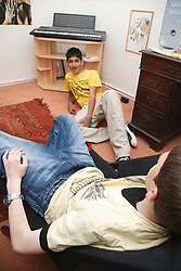 Youths chatting in bedroom.
