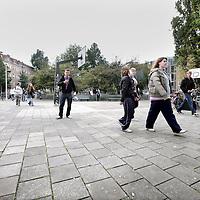 Nederland, Amsterdam , 30 september 2009..Het Timorplein is een centraal gelegen plein in het noord-westkwadrant van de Indische Buurt. De huidige inrichting van het Timorplein is verouderd en sluit niet meer aan bij de gebruikseisen. Het is een plein waar veel gespeeld wordt en een ontmoetingsplek voor de buurtbewoners..Op de foto: jongeren toeristen lopen via het plein naar het Stay in hotel. .The Timorplein (square) has an old fashioned design. The neighbourhood is suffering from nuisance of junks, boozers and the noise of tourists of the Stayokay Hotel.