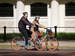 © Licensed to London News Pictures. 04/05/2018. London, UK. Tourists on rental bikes make their way along The Mall in the sunshine in central London. High temperatures are expected to continue throughout the bank holiday weekend. Photo credit: Peter Macdiarmid/LNP