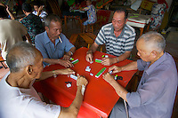 Men playing the  Chinese game Mahjong in a temple in China.
