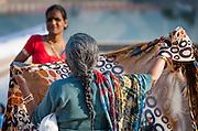 Old Indian woman folding a sari (India)