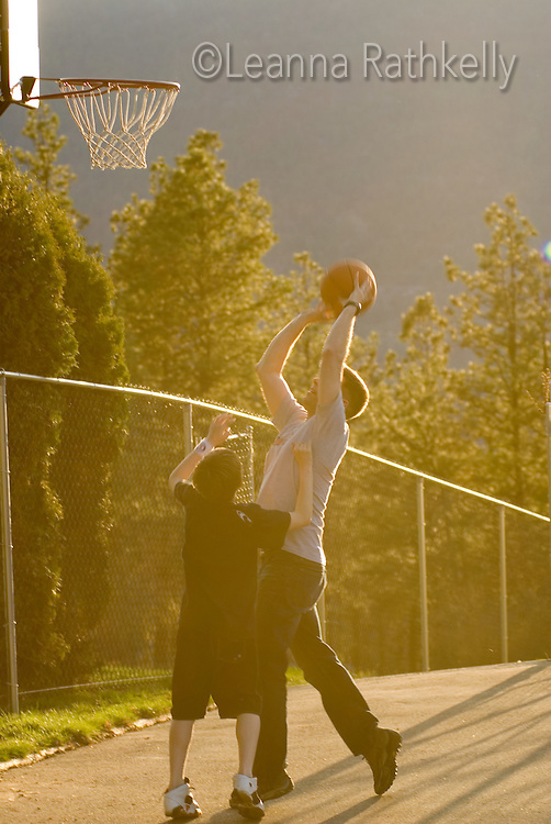 Father and son play driveway basketball, evening