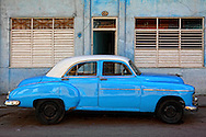 Old blue and white car in front of a blue and white building in Havana Centro, Cuba.