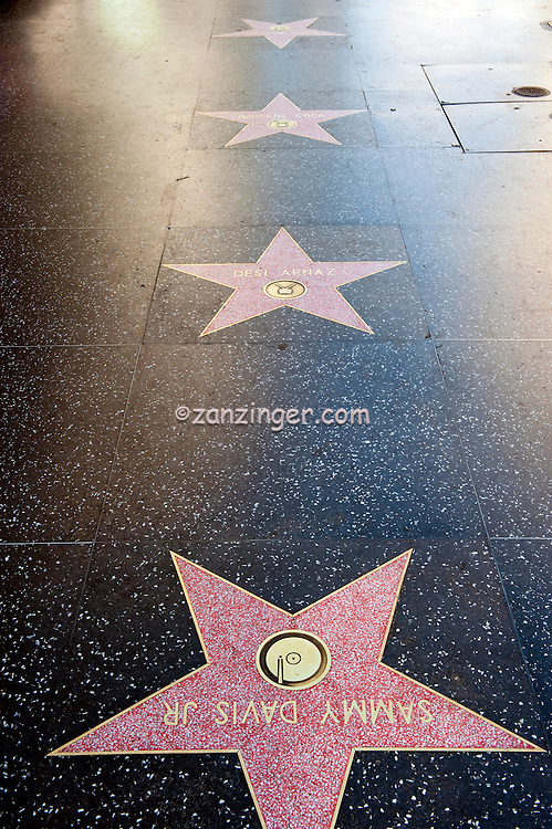 Sammy Davis Jr, Hollywood Walk of Fame, Celebrity Stars, Hollywood, CA, coral-pink terrazzo five-point star rimmed with brass, inlaid into a charcoal-colored terrazzo background. In the upper portion of the pink star field,  round inlaid brass emblem indicates the category