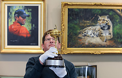 Hamish Wilson from Bonham's with the replica Ryder Cup presented to Sergio Garcia in 2001,  which is expected to fetch up to &pound;8000 GBP in Bonham's sporting goods sale in front of a painting of Tiger Woods which is also in the sale.<br /> <br /> &copy; Dave Johnston/ EEm