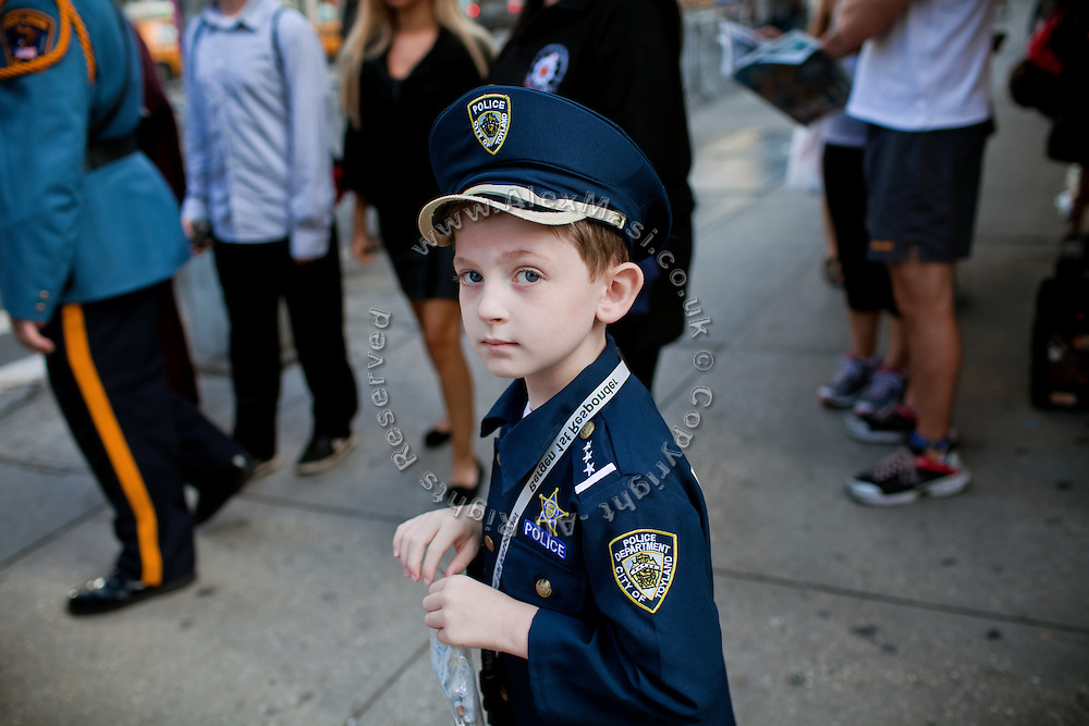 A boy wearing a police uniform is standing on the streets of Lower Manhattan, New York, USA, on the 10th anniversary of the 9/11 attacks on the Word Trade Centre.