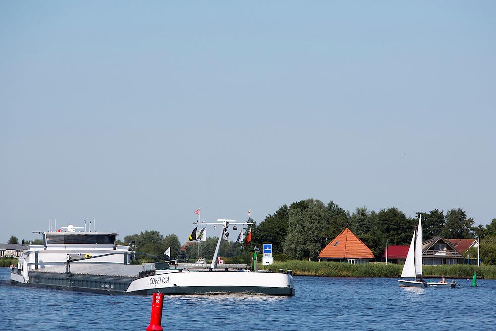 Een zeilboot wacht even tot hij de vaarweg van een binnenvaartschip kan kruisen. Mensen recreëren in het Pikmeer bij het Friese Grou van het mooie zomerweer. Na een kwakkelend begin zet de zomer ineens in. Veel mensen maken gebruik van de mogelijkheid om lekker te gaan varen. De onervarenheid van sommige watersporters leidt geregeld tot gevaarlijke situaties.<br /> <br /> A sailing boat is waiting for a freight sip before passing the Pikmeer near Grou.