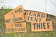 Old Bethpage, New York, USA - July 21, 2012:  When a soldier was accused of doing something wrong, punishment could include wearing a wood sign - like these on the ground - stating what he did, shown at re-creation of  Camp Scott, a Union Army training camp, at Old Bethpage Village Restoration, to commemorate 150th Anniversary of American Civil War, on Saturday, July 21, 2012.
