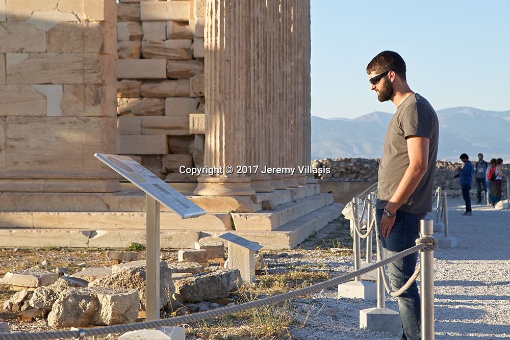 A visitor reads information about the Old Temple of Athena Polias in the Acropolis of Athens. Located between the Parthenon and the Erechtheion, only its foundations remain.