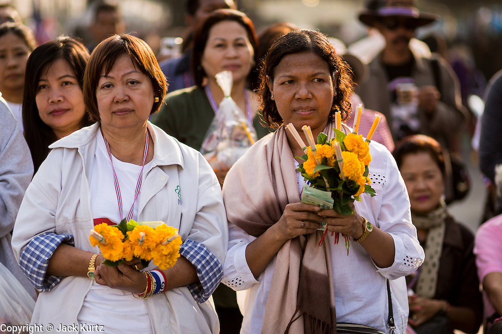 01 JANUARY 2014 - BANGKOK, THAILAND: An anti-government protestors wait for Buddhist monks during a merit making ceremony. Thousands of anti-government protestors are camped out at Democracy Monument in central Bangkok protesting against the government of Yingluck Shinawatra. The protest leader, Suthep Thaugsuban, has called for residents of the Thai capital to rise up against Yingluck. He has promised to shut the city of 12 million down in his final push to overthrow the government. About 100 members of the Thailand's Buddhist clergy visited the protest site Wednesday morning for a special New Year's Day merit making ceremony for the protestors.     PHOTO BY JACK KURTZ