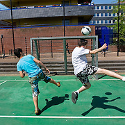 Nederland Rotterdam 24-05-2009 20090524 Foto: David Rozing .                                                                                    .Achterstandswijk Bloemhof, groepje jongeren spelen voetbal op pleintje  straatbeeld, stadbeeld Youth playing soccer on playground court .Foto: David Rozing/