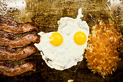 Bacon eggs and hashbrowns cooking on a grittle