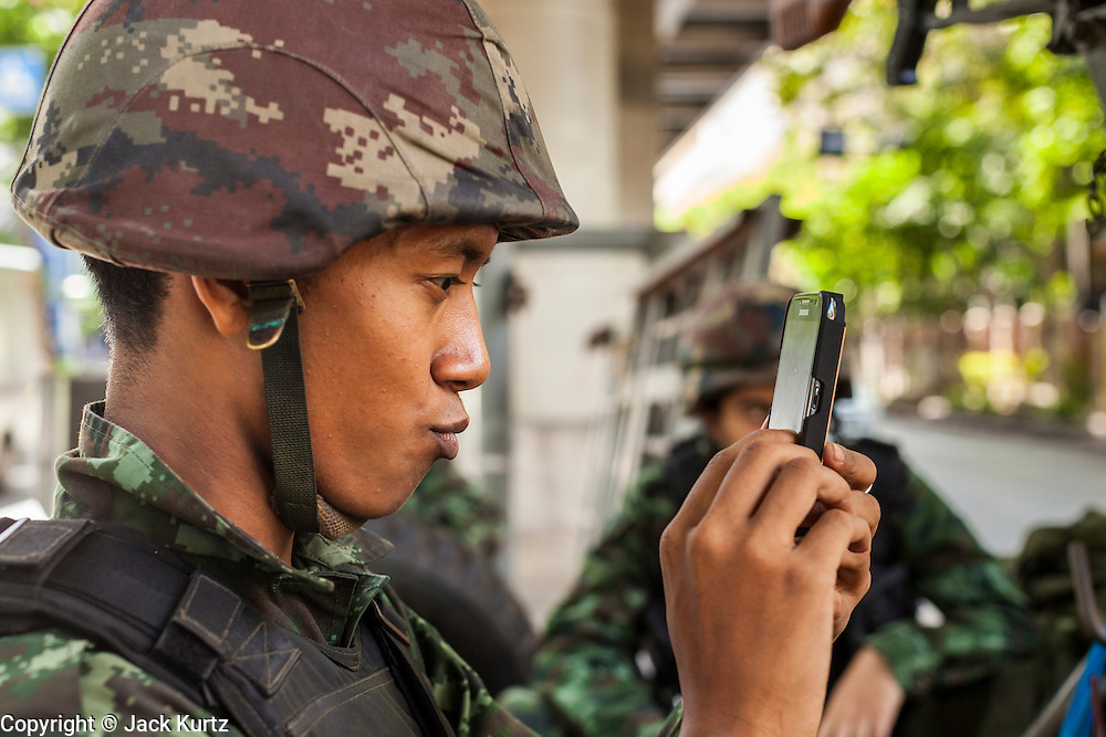 "20 MAY 2104 - BANGKOK, THAILAND: A Thai soldier takes a ""selfie"" at a checkpoint on Rama I Road in Bangkok. The Thai Army declared martial law throughout Thailand in response to growing political tensions between anti-government protests led by Suthep Thaugsuban and pro-government protests led by the ""Red Shirts"" who support ousted Prime Minister Yingluck Shinawatra. Despite the declaration of martial law, daily life went on in Bangkok in a normal fashion. There were small isolated protests against martial law, which some Thais called a coup, but there was no violence.   PHOTO BY JACK KURTZ"