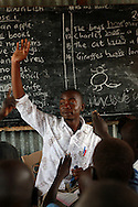 Little Angels school teacher Oscar Noel Bwire, 24, reads a story as part of an English grammar lesson in Bor, South Sudan. Oscar is Kenyan and works as a teacher as well as being one of the leaders of the Young Christian Association at the local Catholic church.  He says that the fact that he is Kenyan makes it easier for him to help build peace between different tribal groups as he has no blood ties to any of them. Sara A. Fajardo/Catholic Relief Services