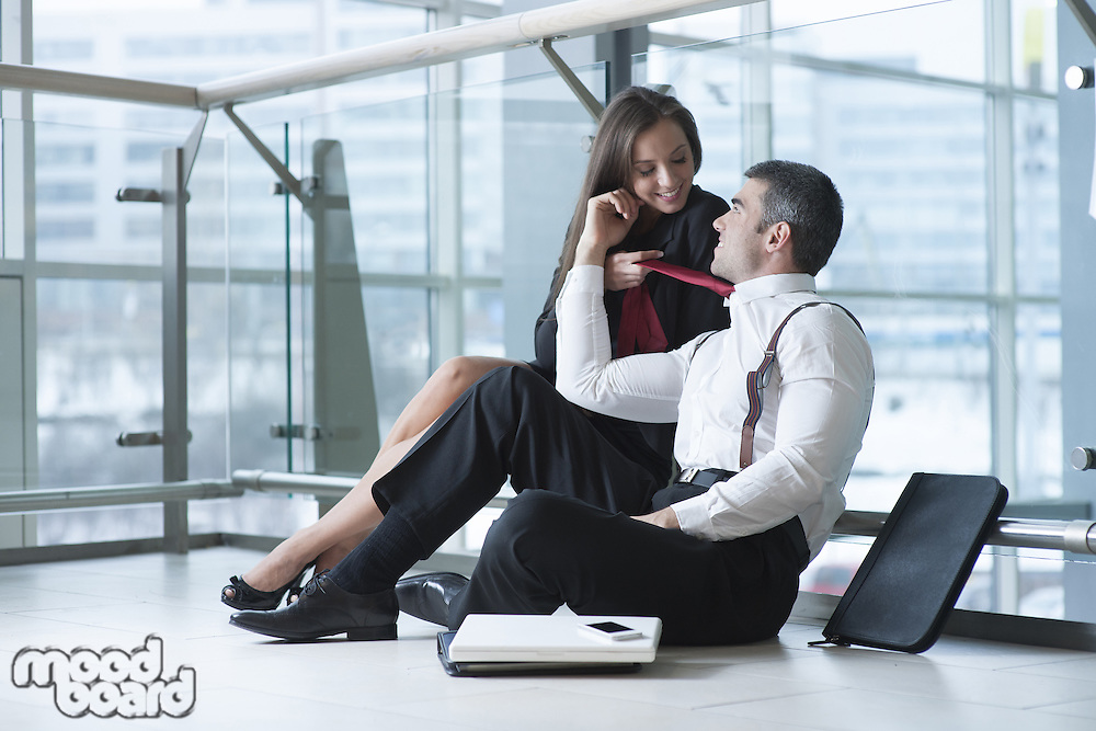 Businesswoman pulls male coworker towards her with his tie