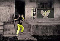 Girl with Yellow Pants Running into Building with UNE Party Sign in San Francisco de Sales. Pacaya Volcano National Park. Image taken with a Nikon D3x and 24 mm f/1.4G lens (ISO 280, 24 mm, f/2.8, 1/200 sec). Raw image processed with Capture One Pro, Nik Viveza 2, Nik Define 2 and Photoshop CS5.