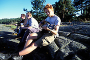 A man sitting outdoors playing a guitar, with two other men in the background. Quart festival, Kristiansands Norway 2000