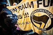 Frankfurt | 07 October 2016<br /> <br /> Am Freitag (07.10.2016) versammelten sich in Wetzlar etwa 80 Neonazis aus dem Umfeld der NPD, von neonazistischen Freien Kameradschaften, dem sog. Freien Netz Hessen und der Identit&auml;ren Bewegung zu einer Demonstration &quot;gegen &Uuml;berfremdung&quot;. Die geplante Demo-Route war von etwa 1600 Anti-Nazi-Aktivisten blockiert, daher wurde den Neonazis eine neue Demoroute durch Altstadt und Innenstadt von Wetzlar vorbei am Wetzlarer Dom zugewiesen. Auch hier stellten sich den Rechten immer wieder Aktivisten in den Weg.<br /> Hier: Polizist vor Transparent mit dem Logo &quot;Antifaschistische Aktion&quot;.<br /> <br /> photo &copy; peter-juelich.com<br /> <br /> FOTO HONORARPFLICHTIG, Sonderhonorar, bitte anfragen!