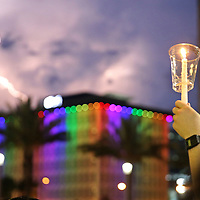 A lighting strike is seen as a person holds up a candle during a vigil at the Dr. Phillips Center for the Performing Arts for the victims of a mass shooting at the Pulse nightclub Monday, June 13, 2016, in Orlando, Florida.  A gunman killed dozens of people in a massacre at the crowded gay nightclub in Orlando on Sunday, making it the deadliest mass shooting in modern U.S. history. (Alex Menendez via AP)