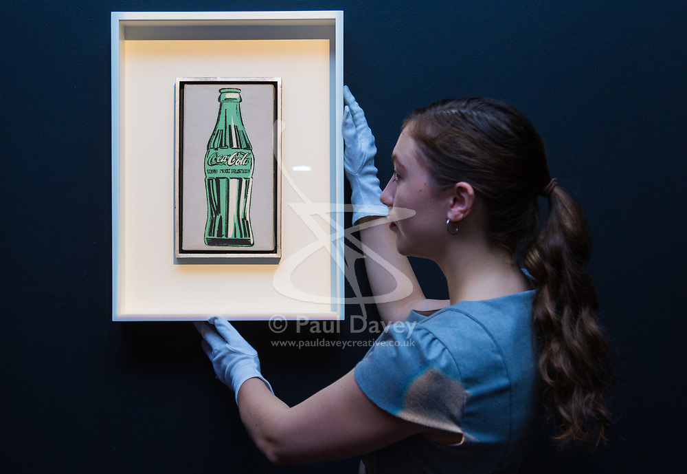 London, September 29 2017. A member of Christie's staff straightens Andy Warhol's Coke Bottle (1962), which is expected to fetch between £1.8 - 2.5 million at auction on October 3rd during Frieze Week at Christie's in London. Coke Bottle is the first branded object depicted by Warhol. © Paul Davey