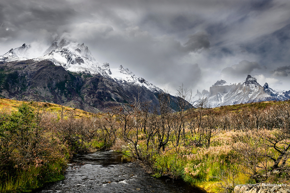 The Cerro Paine Grande and the Cuernos del Paine taken from a bridge over a small stream.