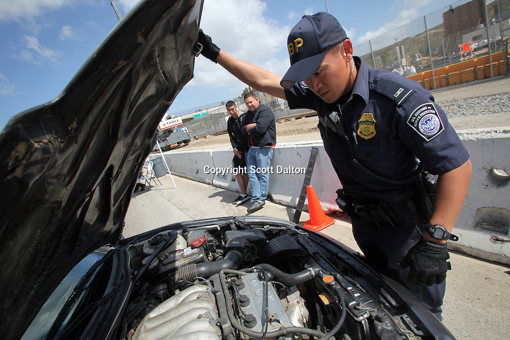 A U.S. Customs and Border Protection agent inspects a vehicle, as the passengers watch, that was heading into Tijuana, Mexico at the San Ysidro border crossing in San Diego, California on April 30, 2010. The US government has stepped up inspections of vehicles crossing over to Mexico in an attempt to try to slow the flow of drug proceeds into Mexico. (Photo/Scott Dalton)