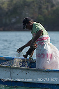 Panamanian fisherman on a small boat haul in nets along the coast of Bona Island, located in Panama Bay.
