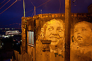 A graffiti depicting residents of Providencia slum share the frame with a lighted transatlantic docked at the Rio port in Rio de Janeiro, Brazil, Friday, March 1, 2013. Morro da Providência is located in the Port area of Rio de Janeiro. The community formed in this location is considered to be the first favela in the city. At the end of the 19th century, the hill was called Morro da Favela, the name that is now used for all irregular constructions.Its first residents were ex-combatants in the Canudos War and settled there around 1897. Some 10 thousand soldiers came to Rio after the government promised them they would receive houses in the then federal capital, but political and bureaucratic red tape led to delays in construction of the residences. So, the ex-combatants began to occupy the hillside temporarily, and ended up staying there.